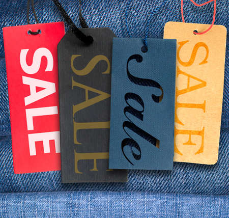 Tags With Sale Sign With Stack of Blue Jeans in Background