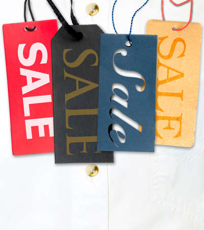 Tags With Sale Sign With Stack of White Shirt in Background