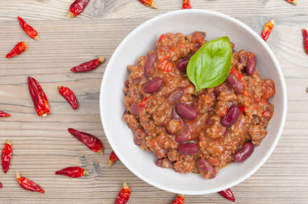 Chilli Con Carne in White Bowl and Chili Peppers
