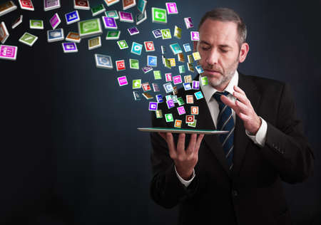Photo pour a mature businessman or salesman shows his pad with lots of apps flying around - image libre de droit