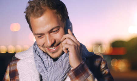 Handsome young man speaking on smart phone at autumn sunset in city. Using smartphone for a phone call, smiling happy wearing urban hipster outfit outdoors at dawn.
