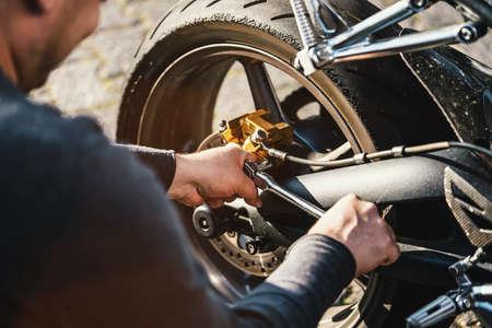 Photo pour Mechanic working on Motocycle in mechanics garage. Repair service. authentic close-up shot - image libre de droit
