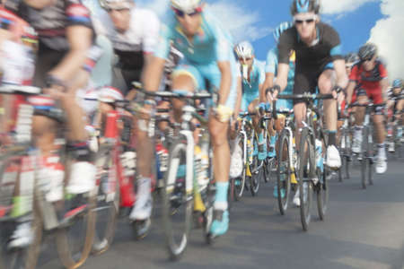 Cycling race participants, motion blur, zoom in, sky in the background