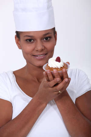 A female baker presenting a pastry.