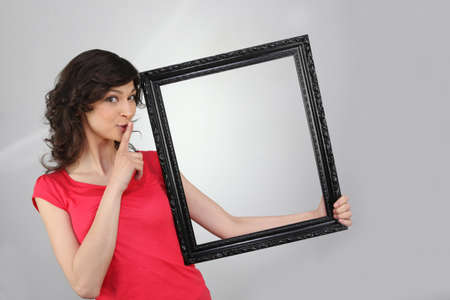 woman holding a picture frameの写真素材