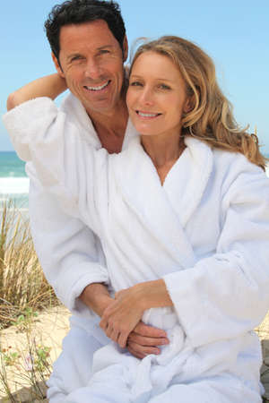 Portrait of couple on dunes in towelling robes