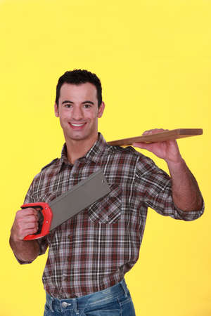A carpenter carrying a plank and a handsaw.