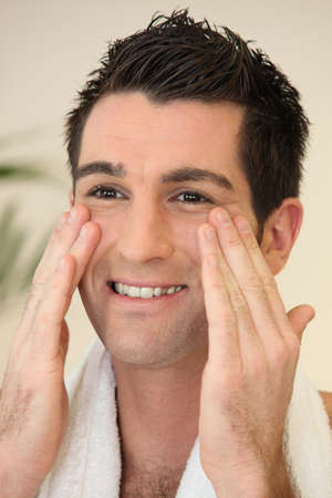 Portrait of a smiling man applying cream
