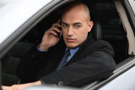 Businessman using a phone in his car
