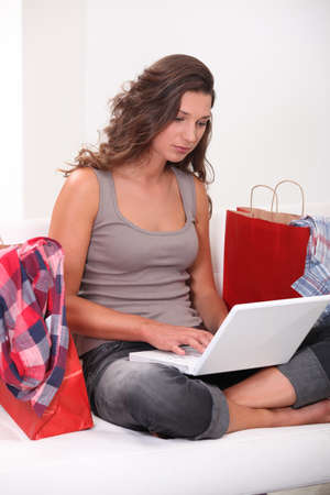 Woman at home shopping on-line surrounded by shopping bags