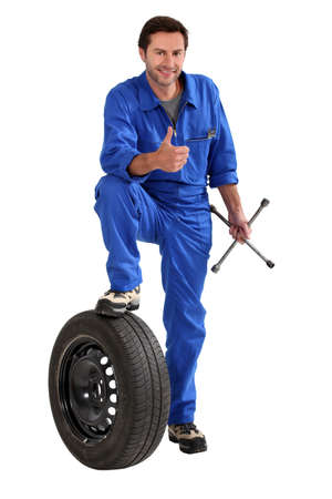 Studio shot of a mechanic with tyre and wrench, giving a thumbs up