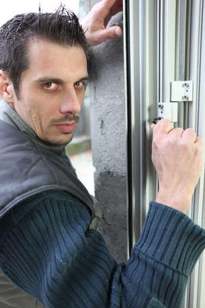 Man fitting a window lock