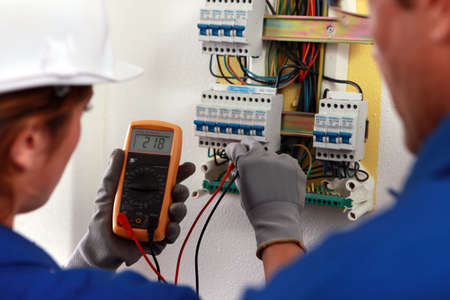 electrician and his apprentice working on a fuse board