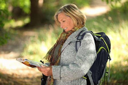 Foto für Older woman looking at a map in a forest - Lizenzfreies Bild