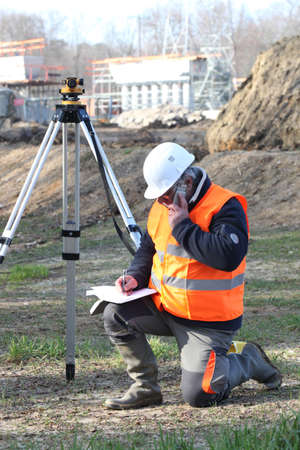 Photo pour A land surveyor writing in his notebook while talking on the phone - image libre de droit