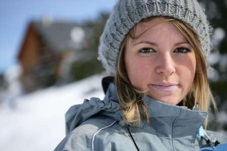 Blond woman stood on snowy mountain
