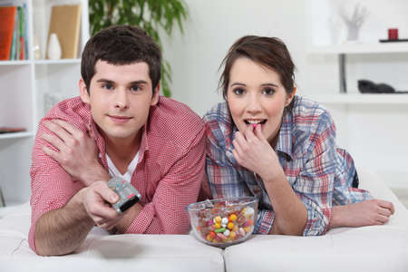 Young couple watching TV with a remote control and bowl of sweets