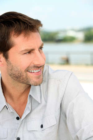 Closeup of cheerful man by the water