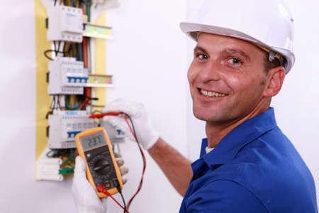 Photo pour Electrician checking a fuse box - image libre de droit
