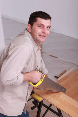 Carpenter sawing wooden flooring