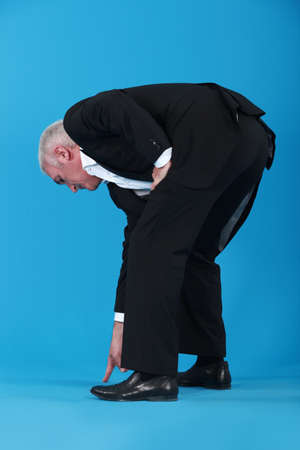 Businessman bent over pointing at shoes