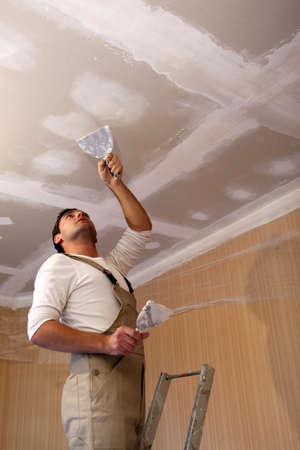 Photo pour Plasterer working on ceiling - image libre de droit