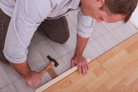 Man renovating the floor with a hammer
