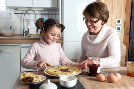 Young girl preparing crepes with her grandmother