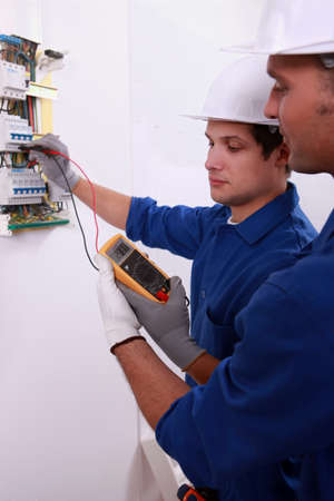 Electricians using multimeter