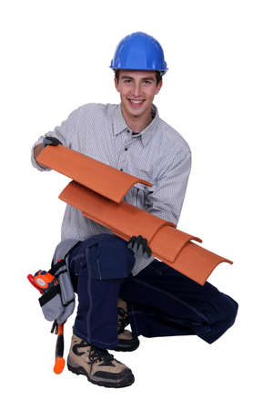 Worker holding roof shingles