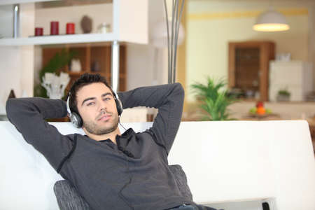 Man relaxing with music on sofa