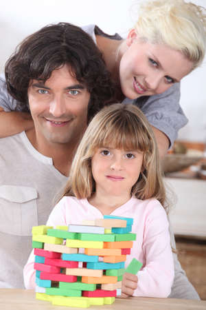 Photo pour Couple playing a stacking game with their daughter - image libre de droit