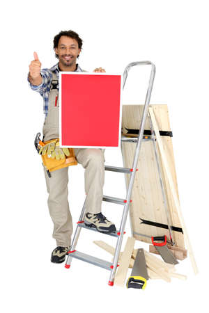 a carpenter doing thumbs up and showing a red panel