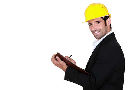 young businessman wearing helmet and taking notes