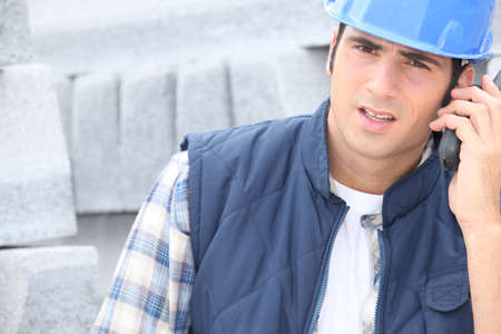 Photo for Construction worker on a call next to a pile of curbing - Royalty Free Image