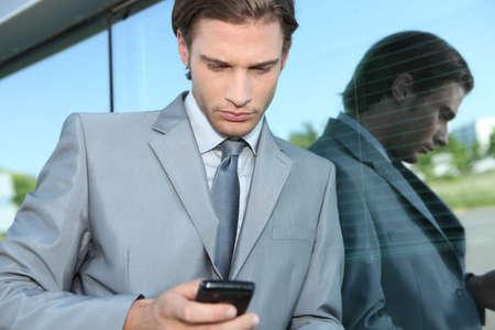 Photo pour Young executive using a mobile phone - image libre de droit