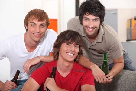 three friends drinking beer at home