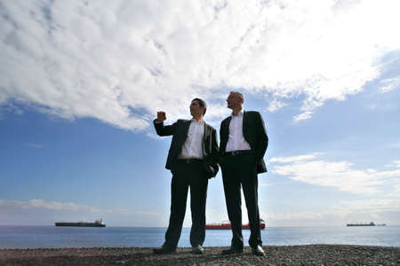 Men in suit chatting at the seaside