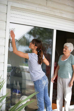 Woman cleaning a glass patio door for an elderly lady