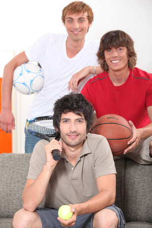 Three male friends with various sporting equipment