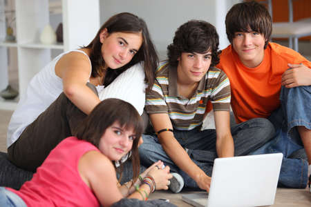 teenagers having fun with a laptop at home