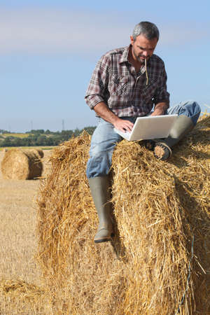Farmer with a laptop on a haystack