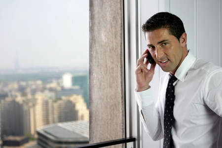 Businessman making call by window