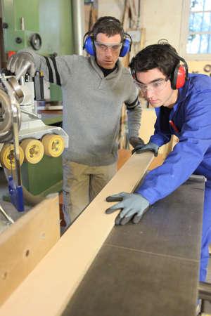 Photo pour Carpenters cutting a plank of wood - image libre de droit
