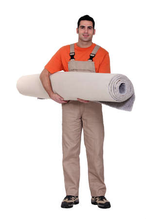 Carpet fitter carrying a roll of carpet