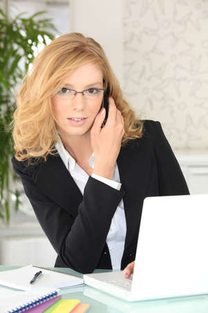 Busy young businesswoman with tousled auburn hair