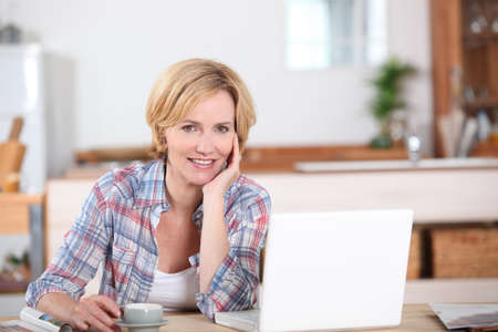 Woman looking at her laptop while drinking a cup of coffee