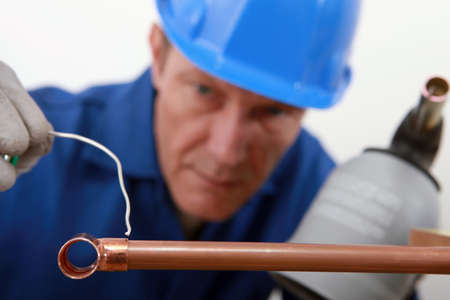 skilled tradesman in blue jumpsuite is soldering a copper pipe
