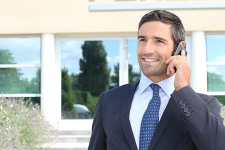 Smiling man in suit talking on cellphone
