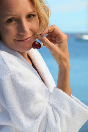 50 years old blonde woman dressed in bathrobe in front of the sea taking cherries in her fingers